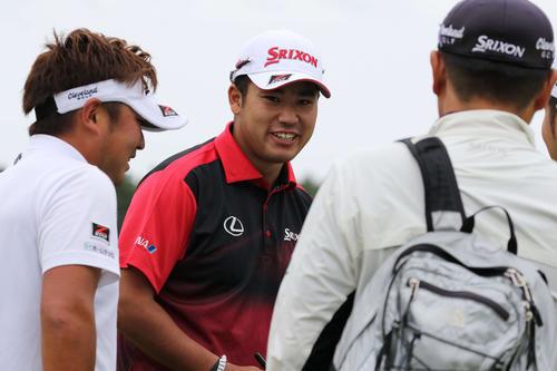 練習場で秋吉(左)と談笑する松山(撮影・亀山泰宏)