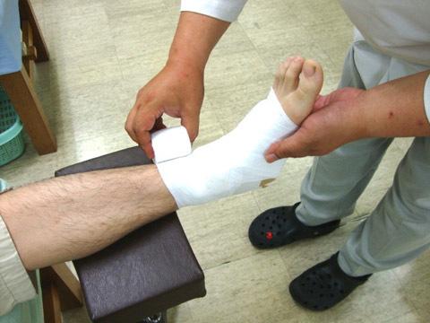 包帯で足首を固定